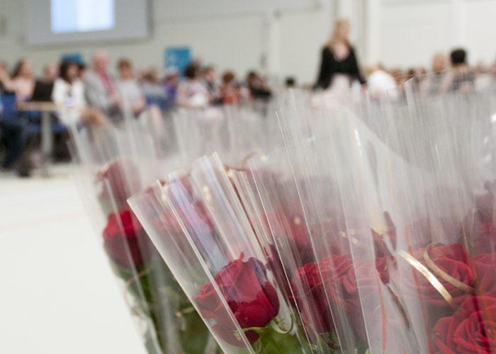 Valmistumisjuhlan sali, taka-alalla ihmisiä tuoleissaan, etualalla yksittäispakattuja ruusuja.