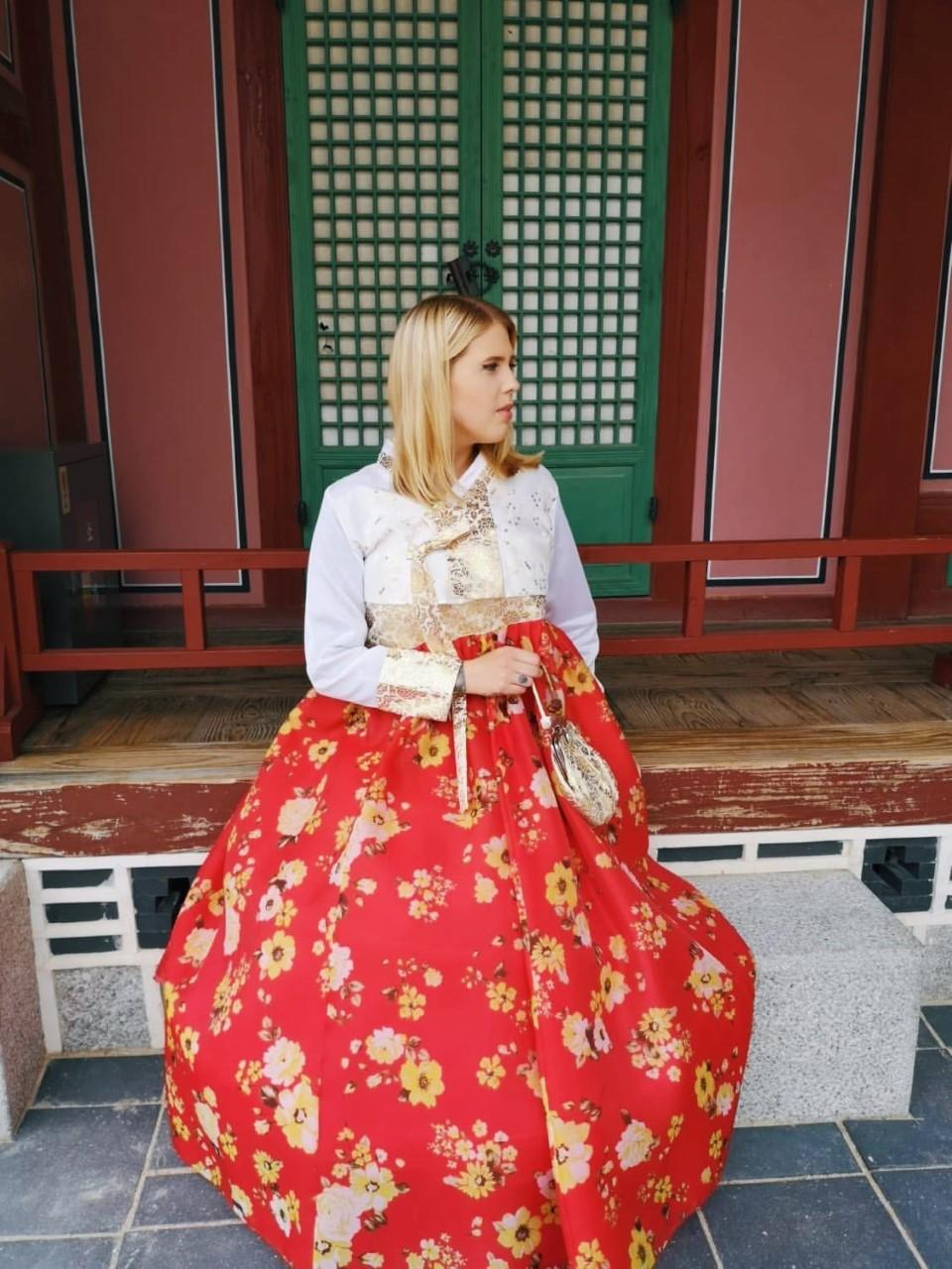 Peppi Wallinkoski istuu rakennuksen edessä, hän on vierailemassa Gyeongbokgungin palatsissa päällään korealainen kansallispuku, Hanbok.