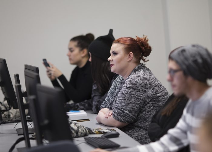 Students of Hospitality Management working with computers in a classroom.