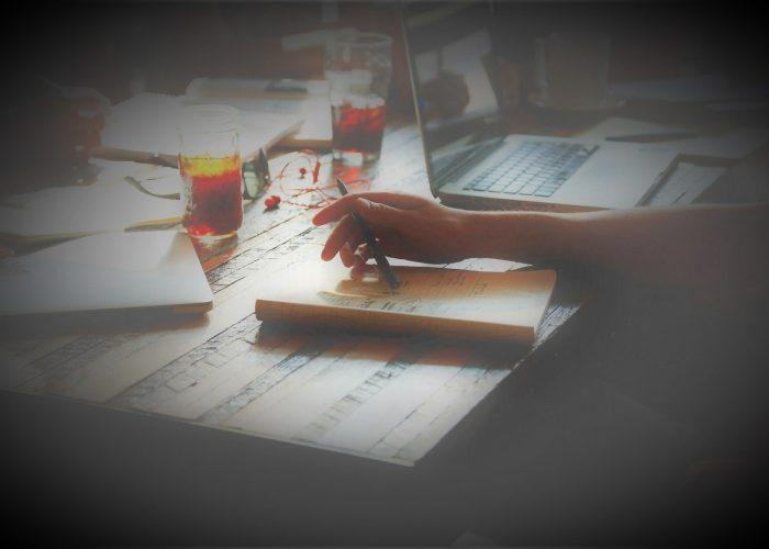 Ihminen tietokoneen ääress, lähikuvassa kynää pitelevä käsi, vihko ja kannettava tietokone.