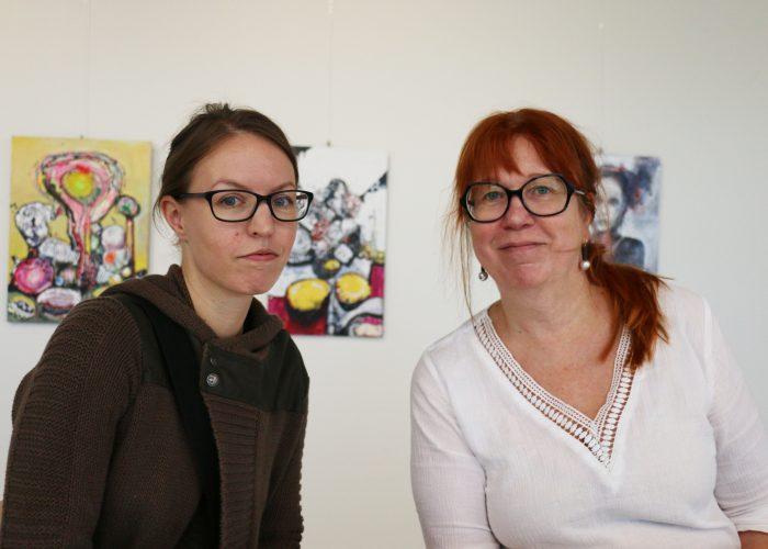 Kaksi SAMK Kankaanpään opiskelijaa poseeraavat taidenäyttelynsä edessä.
