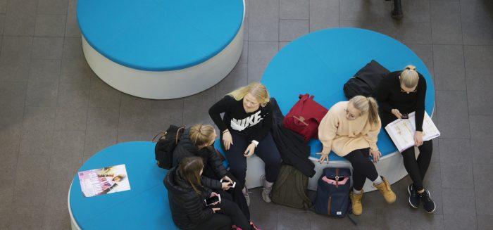 SAMKin opiskelijoita istumassa Porin kampuksen aulassa.