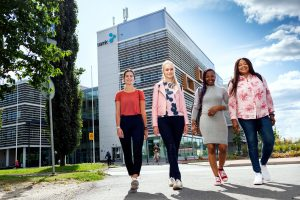 Smiling students walking on the street, SAMK Campus Pori on background.
