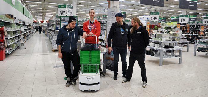 Opiskelijat poseeraavat koripalvelurobotin kanssa Prisman käytävällä.