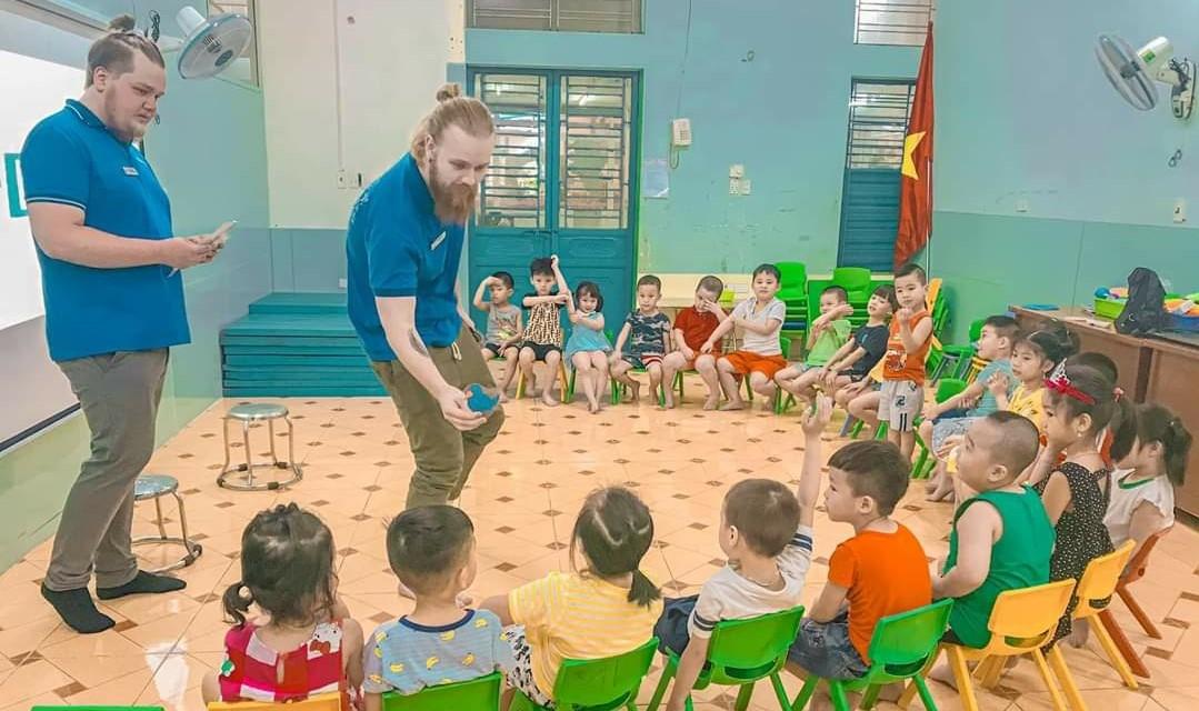 Ilkka Toivonen and Arttu Metsämäki in a teaching situation. Children sit on chairs in an arch.