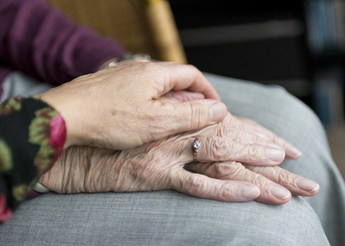 Ikäihmisten pitävät toisiaan kädestä, lähikuva.