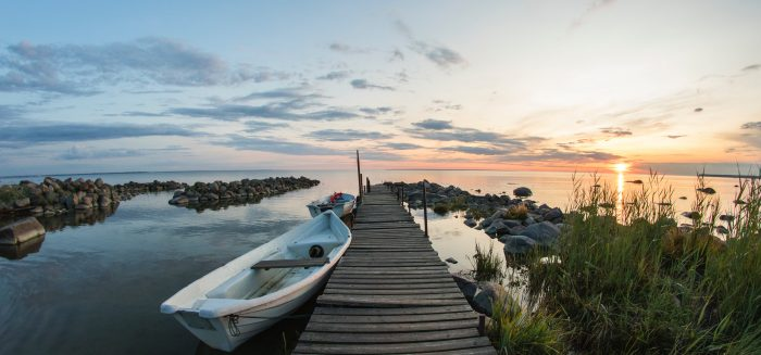 Soutuvene puulaiturin vieressä, taustalla aurinko laskee järven selän taakse.