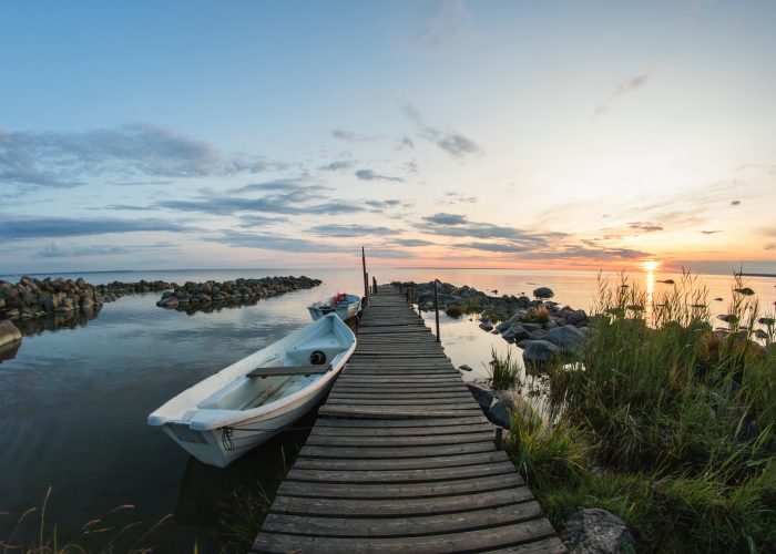 Boat beside pier at sunset.