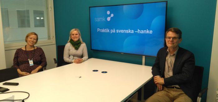 Hankkeen ihmiset istuvat yhdessä pöydän ääressä. Taustalla televisiossa näkyy hankkeen nimi Praktik på svenska.