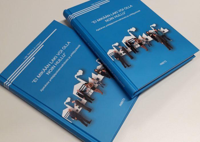 Kaksi painosta jjuri julkaistua kirjaa vierekkäin pöydällä.