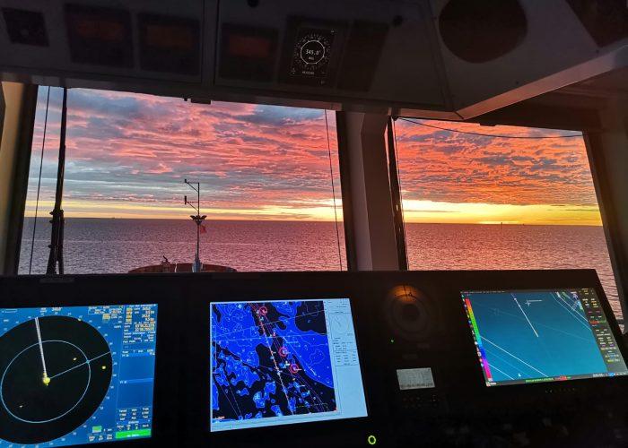 Etualalla laivan komentosillalla olevia mittaristoja. Taustalla kaunis auringonlasku merellä.