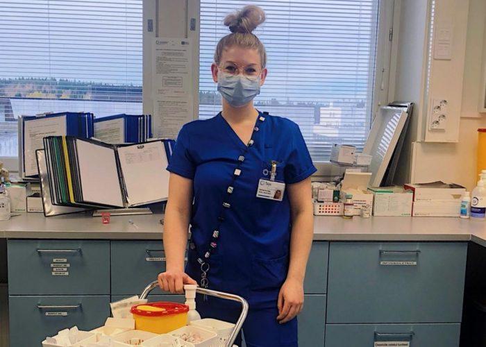 Anni poseeraa hoitopuvussa hoitohuoneessa.