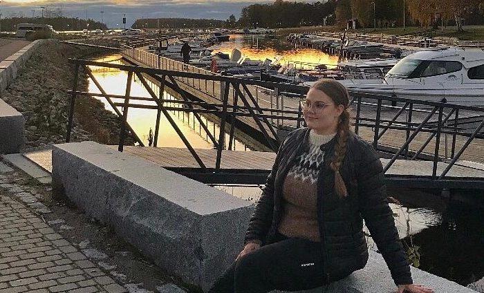 Roosa istuu venelaiturin vieressä.