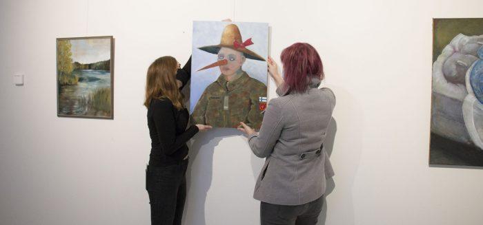 Kaksi naista ripustaa taideteosta SAMKin Porin kampuksen taidekäytävällä.