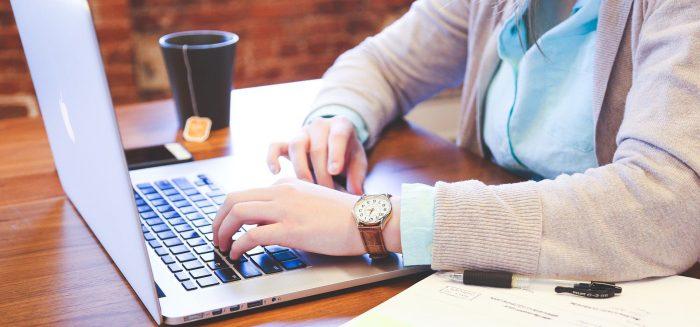 Naisen kädet kannettavan tietokoneen näppäimistöllä.