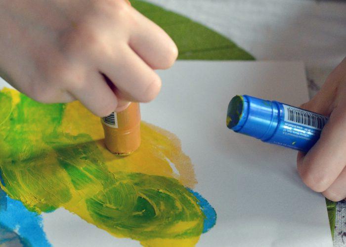 Lähikuva lapsen käsistä ja maalaustarvikkeista.