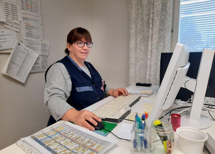 Aila Rantanen istuu työvaatteissa toimistopöytänsä äärellä.