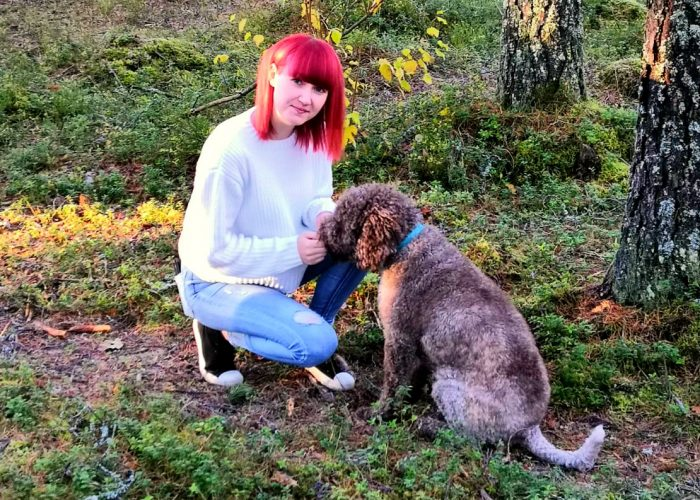 Jonna Hietakangas poseeraa koiransa kanssa metsässä.