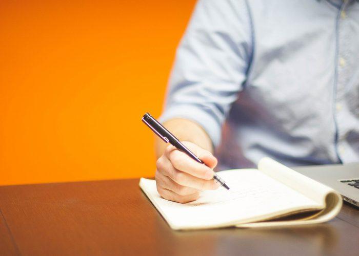 Mieshenkilö kirjoittaa vihkoon, edessään kannettava tietokone/ A man writes in a notebook, in front of him is a laptop.