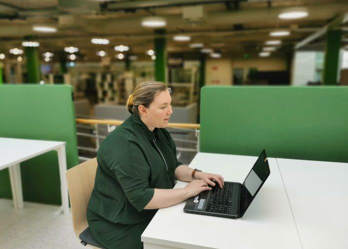 Nadja Grönfors istuu läppärin ääressää SAMK kampus Porin kirjastossa.