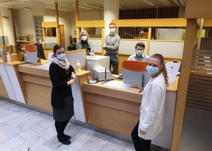 Henkilöitä kasvonaamioissa poseeraa kameralle pankkikonttorin tiskin äärellä.