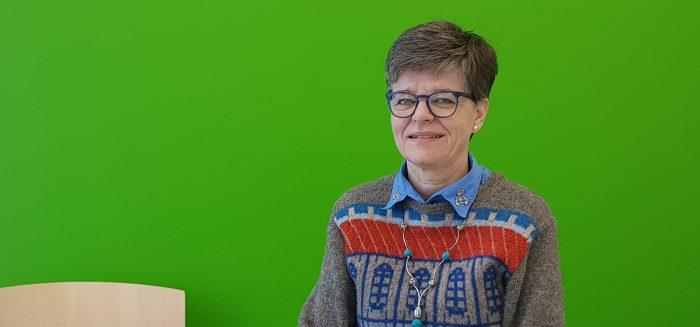 Eija Tuliniemi vihreän seinän edustalla./Eija Tuliniemi in front of the green wall.