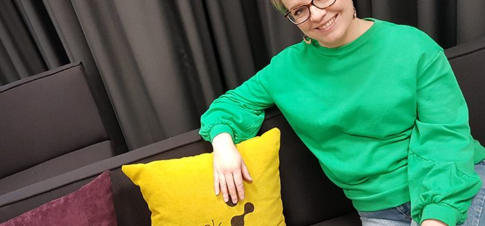 Jonna Koivisto sitting on a couch beside yellow pillow.