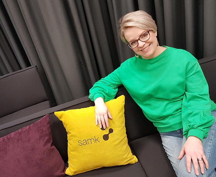 Lehtori Jonna Koivisto istuu harmaalla sohvalla värikkäiden tyynyjen vieressä..