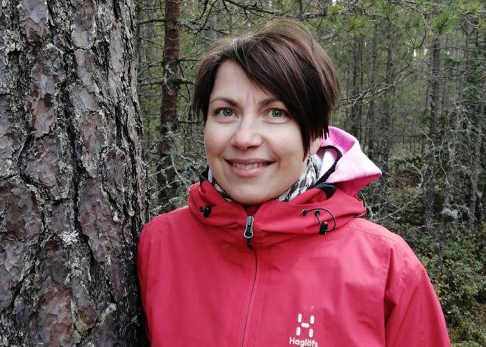 Jenni Kaikkonen nojaa puuhun ja hymyilee.