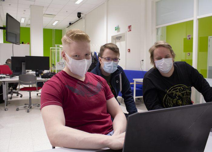 Kolme Robotiikka Akatemian opiskelijaa työskentelee tietokoneella.