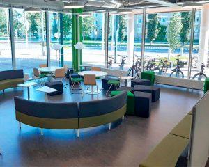Kirjaston kulmatila, jossa tuoleja, pöytiä ja penkkejä.