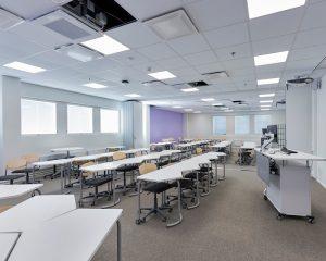Luokkahuone, jossa tuoleja, pöytyä ja esitystekniikkaa.
