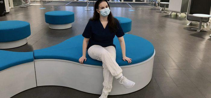 Rosa Leppämäki istuu Porin kampuksen aulassa maski kasvoillaan.
