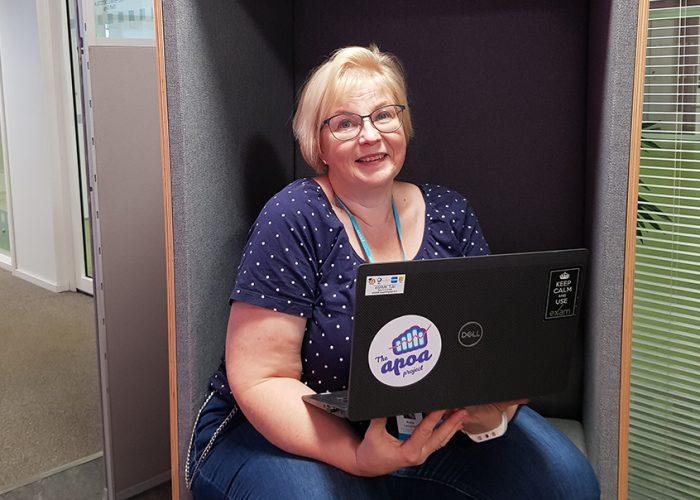 Katja Lempinen istuu Porin kampuksella kannettava tietokone sylissään.