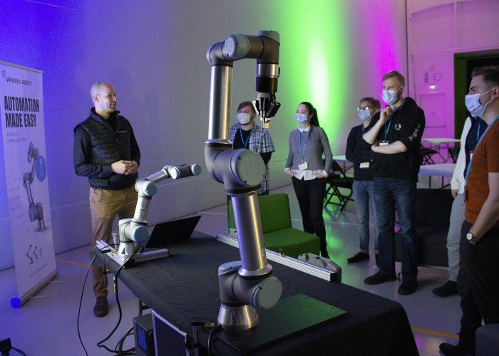 Yrityksen edustaja selostaa opiskelijoille haastetta robotin vieressä.