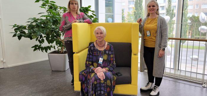 Anne Kärki istuu keltaisella nojatuolilla ja sen takana seisovat Liisa Hannuksela ja Mari Linna.