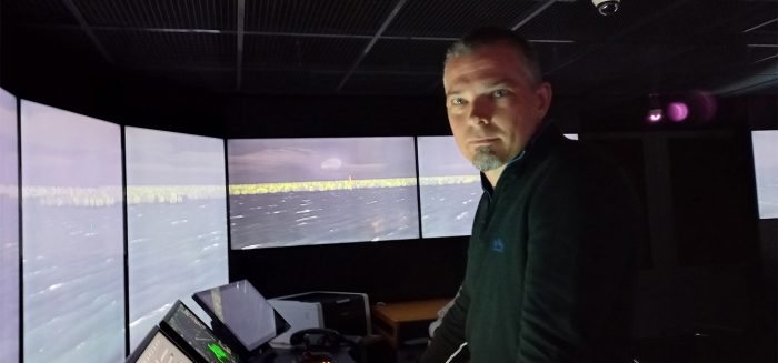 Mies seisoo merenkulun simulaattorissa katse kameraan päin.