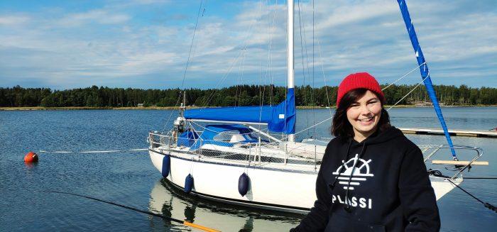 Nuori nainen etualalla ongen kanssa. Taustalla purjevene.