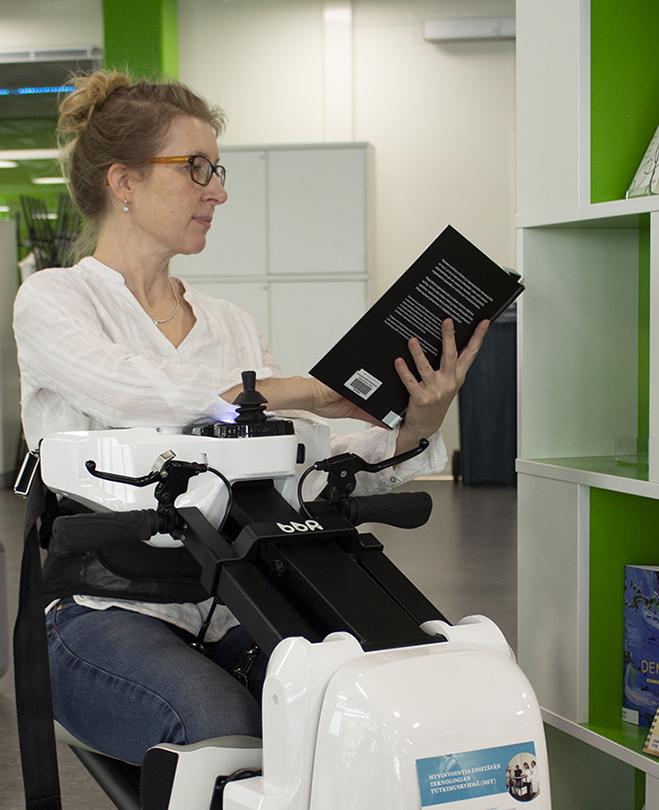 Nainen istuu ajettavan Bangbang-robotin kyydissä ja lukee kirjaa.