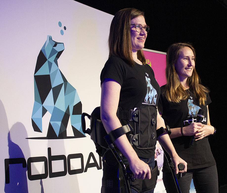 Kaksi naista lavalla RoboAI-viikolla, toisella puettuna eksoskeleton.