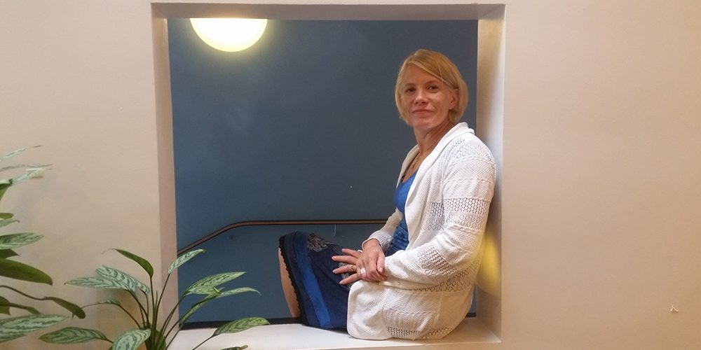 Social psychologist Marjukka Kallio is sitting in the opening of the wall